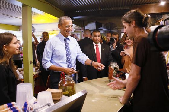 미국 텍사스 '프랭클린 바비큐' 식당에서 결제를 위해 카드를 내미는 버락 오바마 미국 전 대통령. [AP통신]