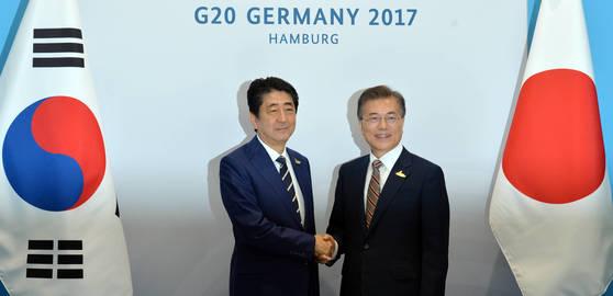 문재인 대통령과 아베 신조 일본 총리가 7일 오전(현지시간) 독일 함부르크 G20 정상회의에서 만나 악수하고 있다.[함부르크=연합뉴스]