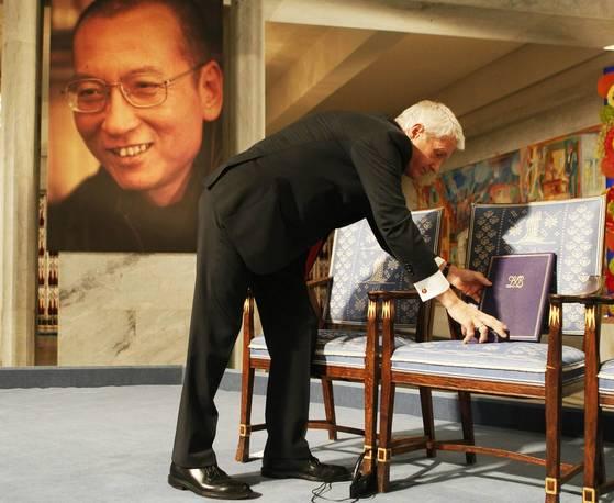 2010년 12월 10일 노벨위원회 위원장인 투르비오른 야글란드가 중국 당국의 불허로 류샤오보가 노벨평화상 시상식에 참석하지 못하자 빈 의자에 메달과 증서를 올려놓고 있다. [AP=연합뉴스]