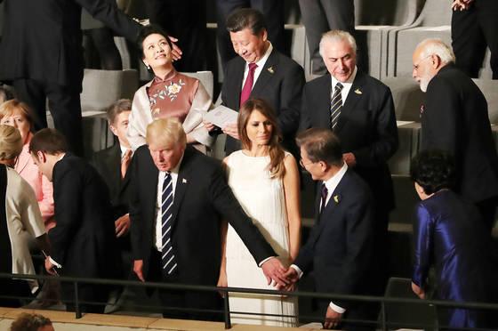 7일(현지시간) 독일 함부르크 엘부필하모니 콘서트홀에서 도널드 트럼프 미국 대통령이 문재인 대통령의 오른손을 잡았다. 시진핑 중국 국가 주석이 뒷줄에서 이 모습을 내려다보고 있다. 잠시 후 시 주석이 씁쓸한 표정을 짓고 있다. [연합뉴스]