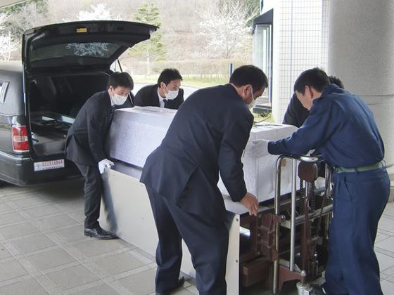 일본 장의사가 무연고 시신이 든 관을 운구차로 옮기고 있다. [사진 지지통신]