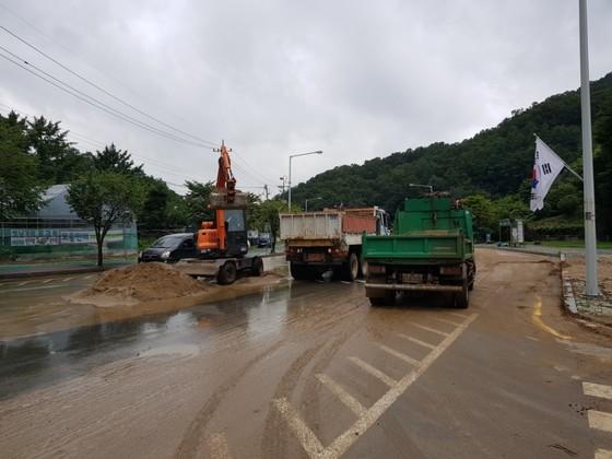 청주시 상당구 용담동 명암저수지에 인근 도로에쌓인 토사를 걷어내는 작업이 한창이다. 최종권 기자