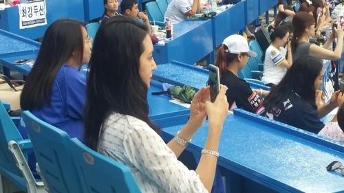 삼부자가그라운드에 선 장면을 휴대전화 카메라에 담는 이승엽의 아내 이송정씨.[연합뉴스]