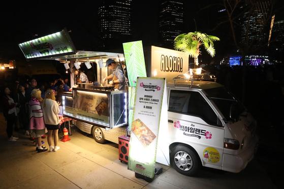 푸드트럭이 한자리에 모이는 '서울 밤도깨비 야시장'에서 시민들이 다양한 푸드트럭 음식을 즐기기 위해 줄을 서서 기다리고 있다. [중앙포토]