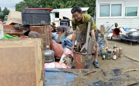 지난 16일 내린 집중호우로 침수 피해를 본 충북 청주시 미원면 주민이 18일 물에 잠겼던 가재도구를 집 밖으로 옮기고 있다. [프리랜서 김성태]