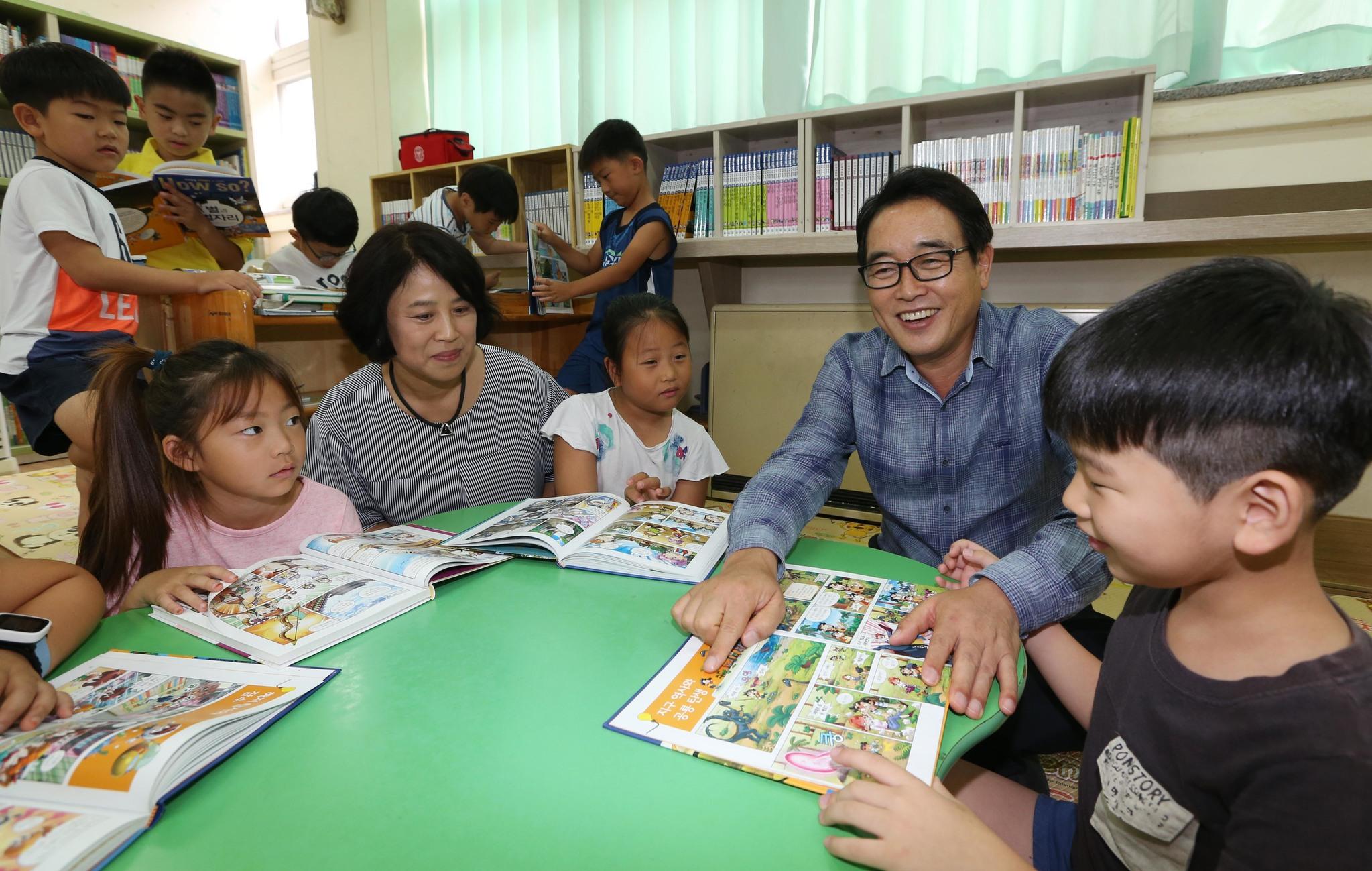 경기도 양평의 개군초등학교의 돌봄교실에서 아이들과 학교 관계자들이 함께 책을 읽고 있다. 19일 문재인 정부는 온종일 돌봄교실을 초등학교 전 학년으로 확대하겠다고 밝혔다. [중앙포토]