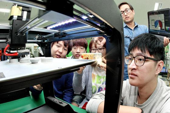 경북 경산의 경일대 캠퍼스 내에 있는 시제품 제작소 '아이 메이크'에서 창업 동아리 학생들이 3D프린터로 스노클링 부품 모형이 만들어지는 과정을 지켜보고 있다. 장비 전문가가 학생을 돕는다. [중앙포토]