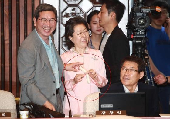 자유한국당 김학용 의원이 22일 의원총회 전 동료 의원들에게 가래떡을 돌리고 있다. [연합뉴스]