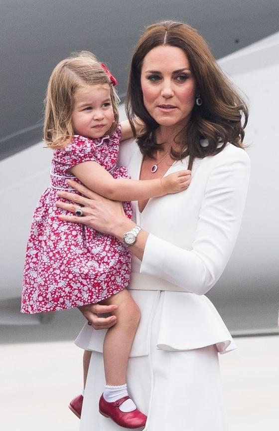 지난 17일 폴란드에 도착해 엄마 캐서린 미들턴 영국 왕세손빈의 품에 안겨 있는 샬럿 공주. 그가 신고 있는 빨간 구두는 삼촌인 해리 왕자가 두 살때 신었던 신발이다. [연합뉴스]