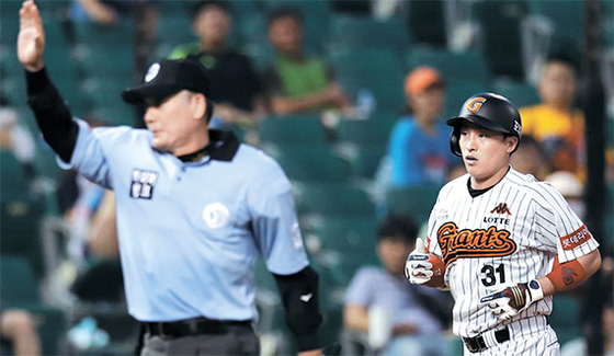 롯데 손아섭(오른쪽)이 지난 20일 삼성전에서 홈런 선을 맞히는 타구(아래사진 동그라미 안)를 날린 뒤 홈으로 들어오고 있다. 하지만 비디오 판독을 통해 2루타로 정정됐다. [울산=연합뉴스]
