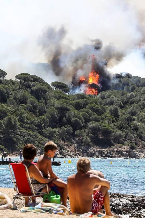 프랑스 남부 연안도시 상트로페 인근에서 해수욕을 즐기던 휴양객들이 25일(현지시간) 가까운 산 위로 치솟은 불길을 바라보고 있다. [AFP=연합뉴스]