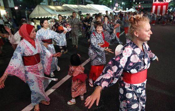 외국인 관광객이 일본의 여름용 의상인 유카타를 입고 전통 춤을 추고 있다. [도쿄 AP=연합뉴스]