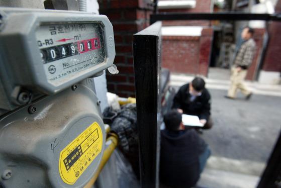 서울 성동구 용답동 주택가에서 도시가스 공급업체 직원이 요금을 연체한 주민과 상담하고 있다. 사진 왼쪽은 숫자판이 멈춰선 가스계량기의 모습. [중앙포토]