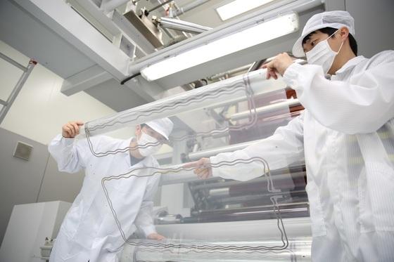 파루 광양 제2공장의 직원들이 냉장고 문에 장착할 필름히터를 살펴보고 있다. 0.2㎜ 두께의 PET 필름에전도성 은나노잉크를 인쇄해 생산한다. 기존 열선 히터보다 10% 이상 전력 을 줄일 수 있다. [사진 파루]