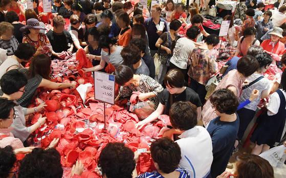 26일 오전 부산진구 롯데백화점 부산본점이 리뉴얼 오픈을 기념해 마련한 빨간 속옷 판매 행사장에서 손님들이 속옷을 고르고 있다. 송봉근 기자