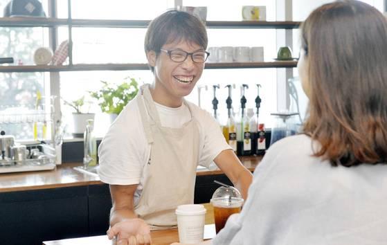 취업 성공 후 기초수급도 포기한 중증장애인 홍성표(27)씨가 25일 오후 천안 한들문화센터 내 중증장애인 고용 카페 '아이갓에브리씽'에서 손님과 반갑게 얘기하고 있다. 프리랜서 김성태