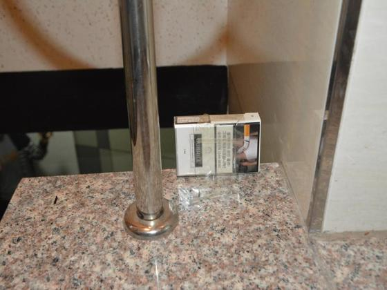 원룸 주거침입 피의자 양씨가 피해자 집 현관 비밀번호를 몰래 촬영하기 위해 휴대전화를 숨기는 목적으로 계단에 붙여둔 담뱃값. 이 담뱃값 뒤에 동영상 줌인 기능을 켠 휴대전화를 테이프로 고정했다. [부산경찰청 제공]