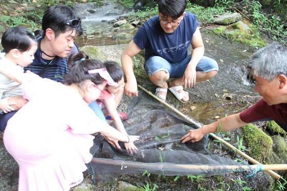 경남 밀양 꽃새미마을 팜스테이 체험객들이 지난 22일 계곡에서 아이들과 함께 잡은 물고기를 놓고 이야기를 나누고 있다. [위성욱 기자]