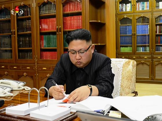 김정은 북한 노동당 위원장이 지난 4일 화성-14형 미사일 1차 시험 발사를 앞두고 발사를 지시하는 서명을 하고 있다. [사진=노동신문]