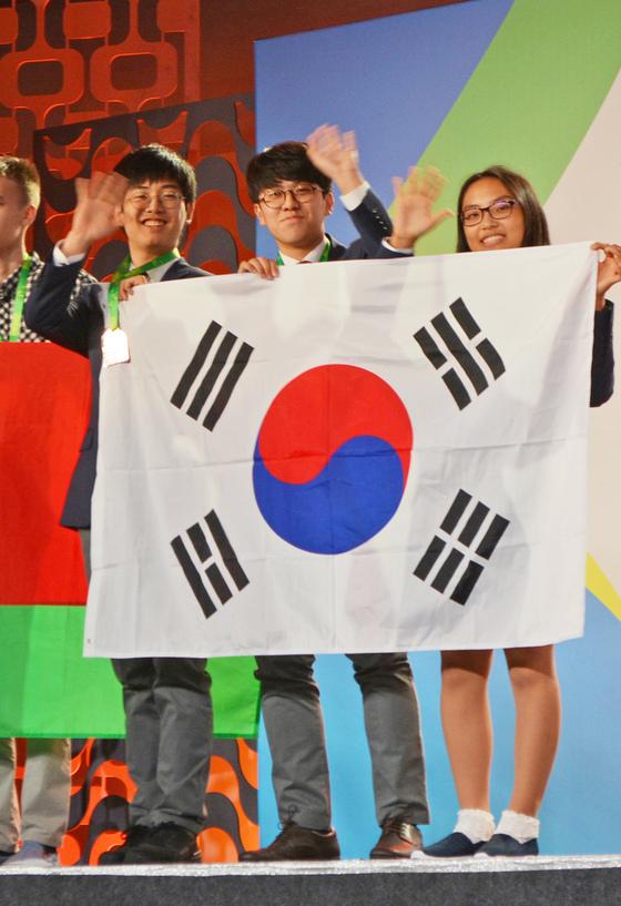 지난 22일(현지시간) 브라질 리우데자네이루 '2017년 국제수학올림피아드' 시상식에서 종합 1위 한국대표팀의 안정현·김세훈·김다인(왼쪽부터) 학생이태극기를 들고 손을 흔들고 있다. [연합뉴스]