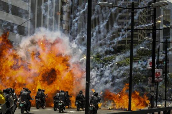 베네수엘라 제헌의회 선거가 실시된 30일(현지시간) 수도 카라카스에서 시위대의 사제 폭발물이 터지면서 기동경찰대를 덮치고 있다.[EPA=연합뉴스]