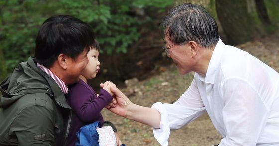 문재인 대통령이 여름 휴가 이틀째인 지난달 31일 강원도 평창 오대산 상원사길 등반 중 만난 어린이의 손을 잡아주고 있다. [사진 청와대]