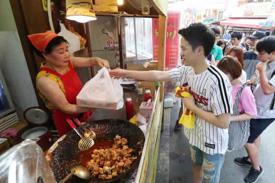 닭강정 가게 앞에는 야구 유니폼을 입은 젊은 고객들이 경기 시작 1시간 전부터 줄을 섰다. 김경록 기자