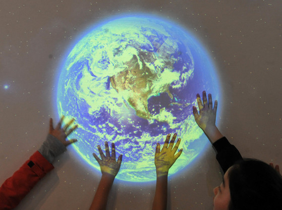 지구가 제공하는 생태자원보다 더 많은 양을 인류가 소비하면서 지구 생태계는 위기에 처했다. 지구의 날인 4월 22일 대전중앙과학관을 찾은 어린이들이 지구 소개 영상물을 손으로 만져보고 있다. [중앙포토]