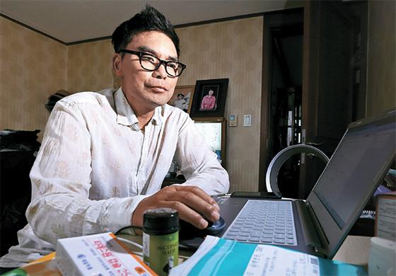 """침샘암 환자인 백영묵씨가 집에서 컴퓨터로 치료약을 검색하고 있다. 백씨는 """"전이된 침샘암에 관한 정보를 얻을 수 있는 곳이 없어 혼자 찾아보고 있다. 창문 하나 없는 캄캄한 독방에 갇혀 있는 기분""""이라고 말했다. [임현동 기자]"""