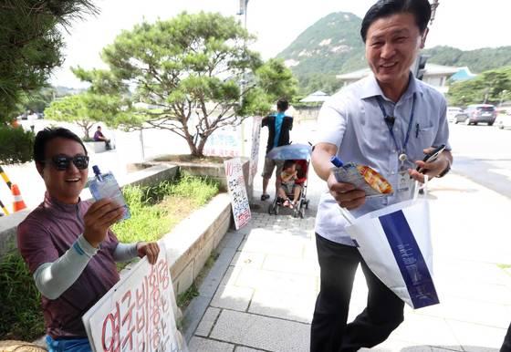 청와대 외곽 경호를 담당하는서울 경찰청 소속 한 직원이 3일 청와대 분수대앞 광장 인근에서 1인 시위를 벌이고 있는 시민에게 차가운 음료를 전달하고 있다. 김상선 기자