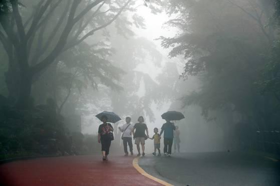 장맛비가 내린 지난달 28일 시민들이 비로 안개가 낀 서울 남산길을 걷고 있다. 김상선 기자