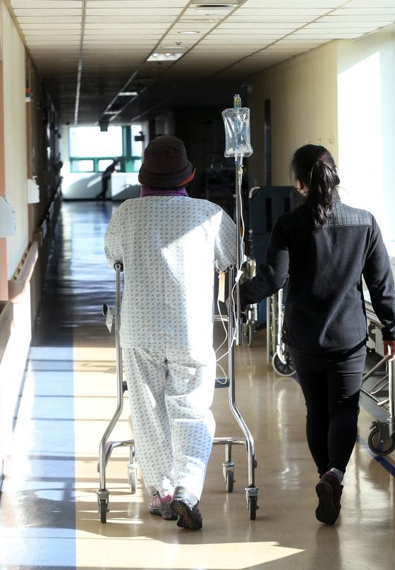 일산 국립암센터 입원 병동에서 한 여성 암환자가 링거 주사를 맞으며 운동 삼아 병원 복도를 돌고 있다.[중앙포토]