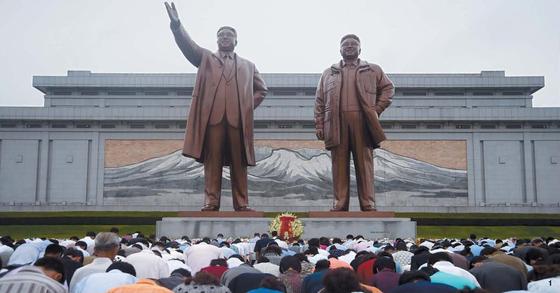 북한 김일성 주석 사망 23주기를 맞은 7월 8일 평양시 만수대 김일성·김정일 부자 동상 앞에서 평양 시민들이 고개를 숙이고 있다. [중앙포토]