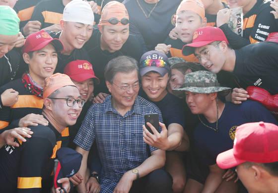 문재인 대통령이 지난 3일 진해 해군사관학교 내 거북선 모형 함을 방문하러 가던 중 만난 해군사관생도들과 기념사진을 촬영하고 있다. [청와대 제공]