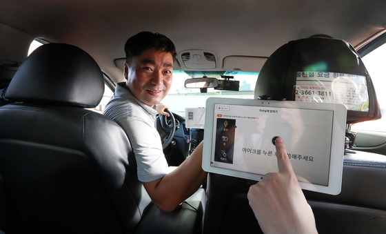 청각 장애인 택시기사 최철성씨가 지난 16일 택시에서 뒷좌석을 향해 미소짓고 있다. 승객은 택시 안에 설치된 태블릿 PC를 통해 기사에게 목적지를 전달할 수 있다. 우상조 기자
