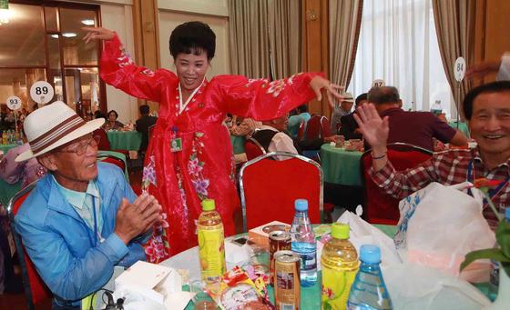남북 이산 상봉 이틀째인 21일 금강산호텔에서 열린 단체상봉 에서 남측 최기호(83) 할아버지가 북측의 조카 최광옥(53)씨의 춤을 보며 박수를 치고 있다. [사진공동취재단]