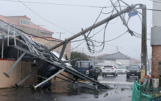 제19호 태풍 솔릭이 제주를 강타한 23일 오전 제주시 삼양동에 있는 전봇대가 강풍에 맥없이 쓰러져 있다. 이로 인해 주변 건물이 일부 파손됐으며 일대가 정전됐다. [연합뉴스]