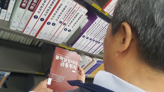 국회도서관 이용자가 서가에서 골라든 경제 서적을 보고 있다. 김동호 기자