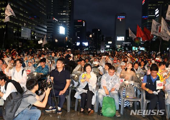 24일 오후 서울 종로구 광화문광장에서 열린 항공재벌 갑질격파 시민행동 촛불문화제에서 참석자들이 가면을 벗는 퍼포먼스를 하고 있다. [뉴시스]