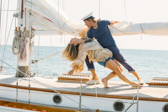 젊은 시절 도나를 연기한 배우 릴리 제임스와 빌을 연기한 조쉬 딜란이 배 위에서 연기를 하고 있다. [사진 UPI코리아]