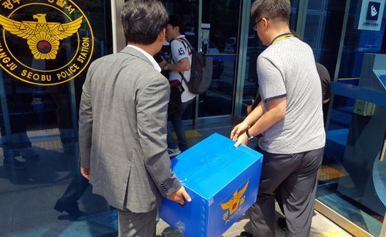 고3 시험지 유출 사건을 수사하는 광주 서부경찰서 소속 수사관이 사건이 발생한 광주 한 고등학교에서 챙겨온 압수품을 옮기고 있다. [연합뉴스]