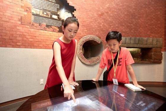 김신희 학생모델이 근대 배수로 모형 가상 체험을 위해 터치스크린 버튼을 누르고 있다.