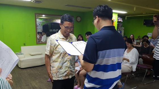 전주 샛별야학 고등반 김병초(67)씨가 변상경(41) 교장에게서 졸업장을 받고 있다. [사진 샛별야학]