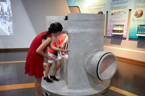 김신희(왼쪽) 학생모델·유용민 학생기자가 서울하수도과학관 전시실의 하수도 모형을 보고 있다.