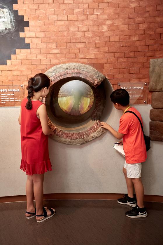 김신희(왼쪽) 학생모델·유용민 학생기자가 서울광장 지하 배수로 모형을 보고 있다.