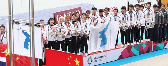 자카르타·팔렘방 아시안게임에 출전한 카누 용선 남북 단일팀이 여자 500m에서 금메달을 따냈다. 시상식에서 '아리랑'을 부르고 있는 선수들. [연합뉴스]