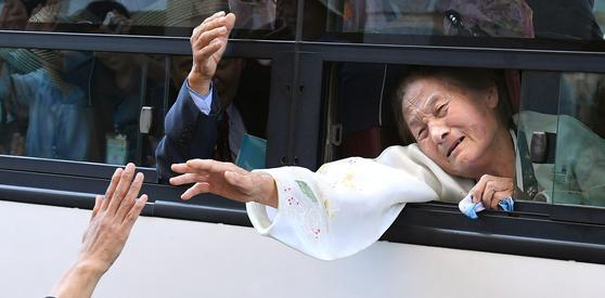 이산가족 상봉 행사 마지막 날인 26일 북측 가족들이 금강산호텔에서 버스를 타고 먼저 떠나며 작별인사를 하고 있다. [사진공동취재단]