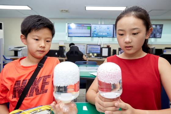 유용민(왼쪽) 학생기자·김신희 학생모델이 여재를 관찰하고 있다.