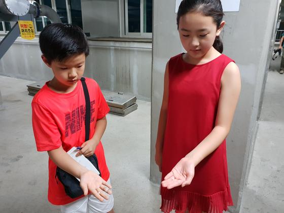 유용민(왼쪽) 학생기자·김신희 학생모델이 제1처리장 생물막여과조 앞에서 여재를 관찰하고 있다.