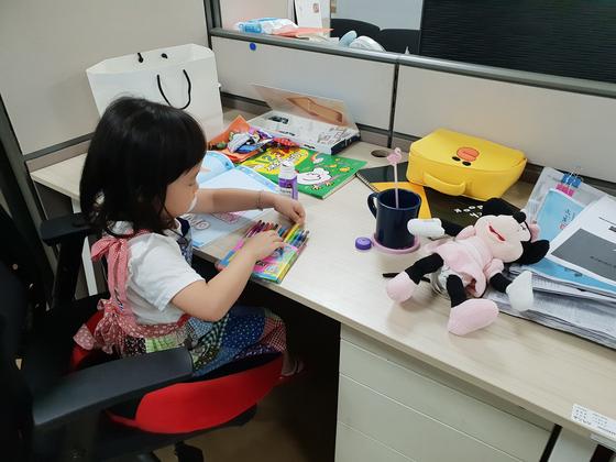 엄마 따라 회사에 출근해 맞은편 책상에 자리잡은 아이는 종일 그림을 그리거나 색칠놀이를 하며 한 자리에서 엄마를 기다렸다. [사진 서영지]